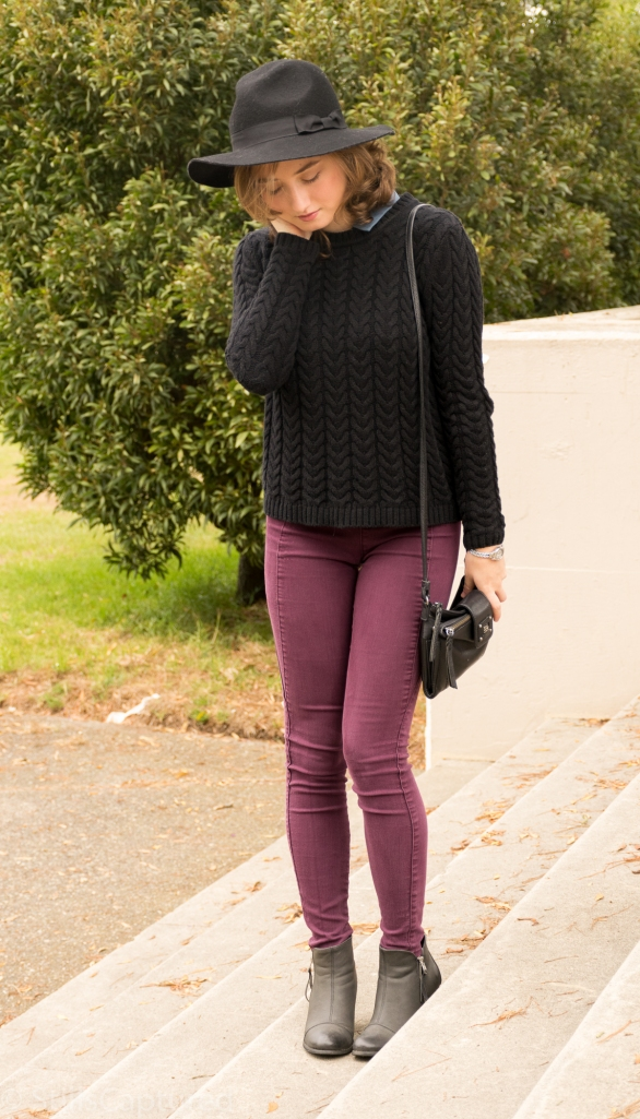 Black hat, black sweater with blue collar, purple pants, black booties, cross body purse