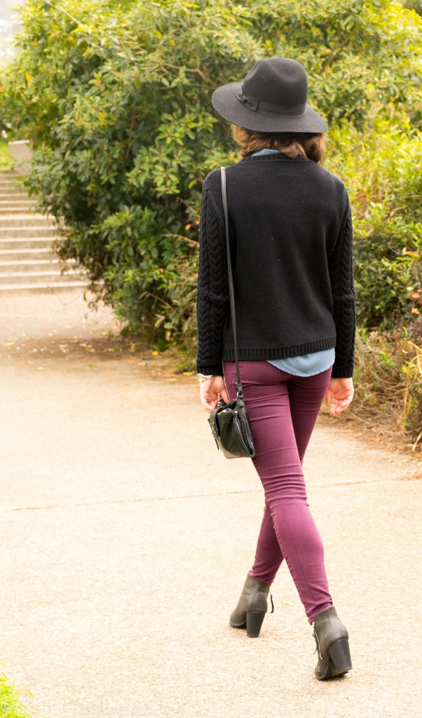 Black hat, black sweater with blue collar, eggplant pants, black booties, long bob, cross body purse