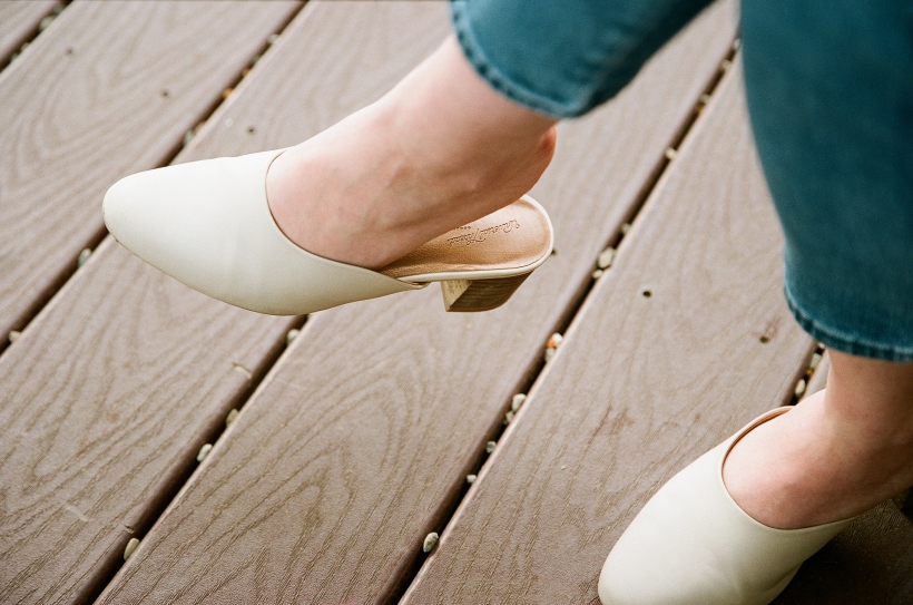 Picture of a woman's mule shoes and cropped denim